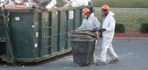Technicians Removing Fire Damaged Debris To Dumpster